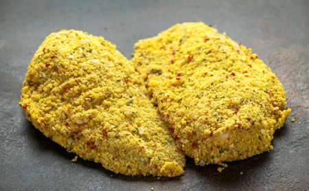 Breaded ready to cook fresh raw chicken Kievs on dark background Stock Photo