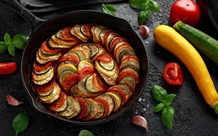 Ragoût de légumes ratatouille avec courgettes, aubergines, tomates, ail, oignon et basilic. sur poêle en fonte. Cuisine traditionnelle française. Banque d'images