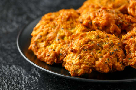 Indian takeaway food, spicy onion bhajis on black plate Stock Photo