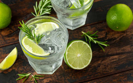 Gin and Tonic Alcohol drink with Lime, Rosemary and ice on wooden table Archivio Fotografico