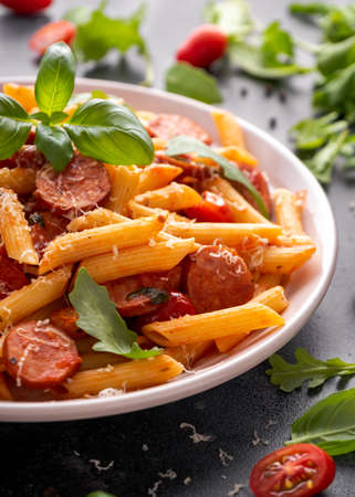 Sausage penne Pasta with tomato sauce and fresh herbs Stock Photo