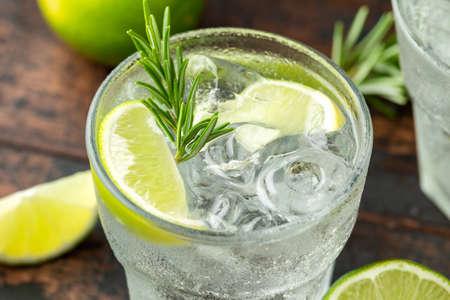 Boisson alcoolisée au gin et tonique avec citron vert, romarin et glace sur table en bois.