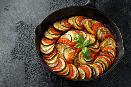 Guiso de verduras de pisto con calabacín, berenjenas, tomates, ajo, cebolla y albahaca. sobre sartén de hierro fundido. Comida tradicional francesa