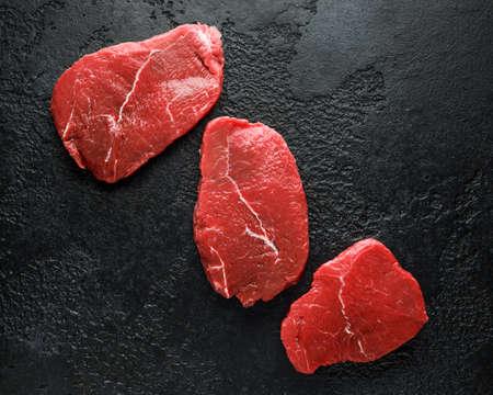 Fresh Raw braising beef steak on black rustic background.