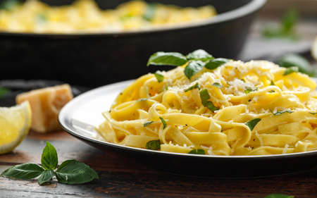 Pasta al Limone, Lemon with basil and parmesan cheese on wooden table.