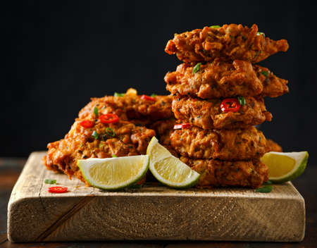 Indian takeaway food, spicy onion bhajis served with chili yoghurt dip and lime wedges on wooden board.