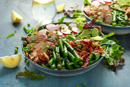 Cobb salad bowl with grilled chicken breast, asparagus, avocado, radishes and bacon Foto de archivo - 129859305