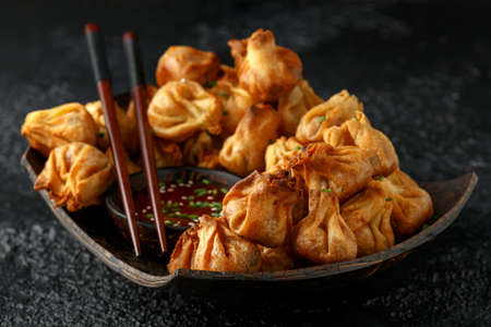 Chinese takeaway finger food Vegetable wontons with sweet chilli dip sauce and chop sticks.