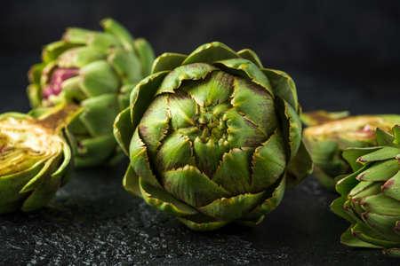 Frische rohe biologisch angebaute Artischockenblütenknospen auf dunklem Hintergrund. Standard-Bild