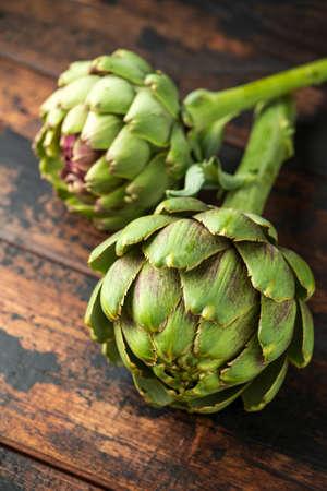 Fresh raw organically grown artichoke flower buds on wooden table.