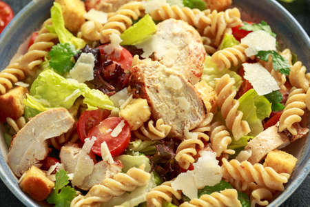 Caesar Salad Pasta with chicken, tomato, parmesan cheese and vegetables. Foto de archivo - 129859349