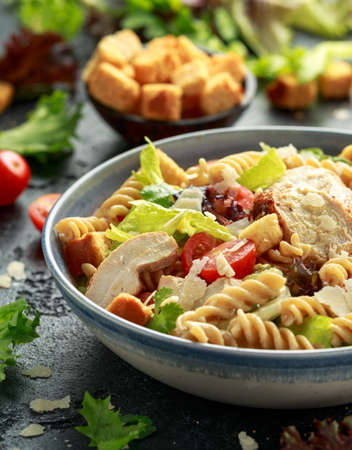 Caesar Salad Pasta with chicken, tomato, parmesan cheese and vegetables. Foto de archivo - 129859350