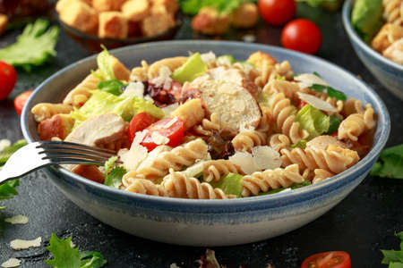 Caesar Salad Pasta with chicken, tomato, parmesan cheese and vegetables.