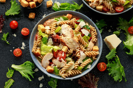 Caesar Salad Pasta with chicken, tomato, parmesan cheese and vegetables. Foto de archivo - 129859358