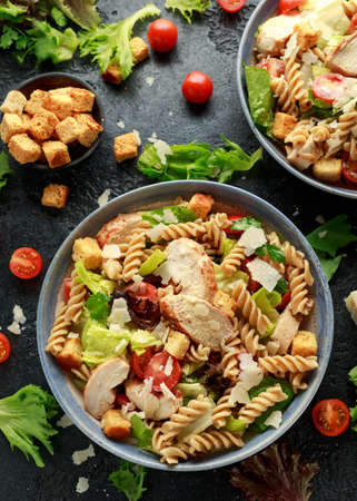 Caesar Salad Pasta with chicken, tomato, parmesan cheese and vegetables. Foto de archivo - 129859359