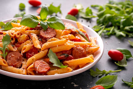 Sausage penne Pasta with tomato sauce and fresh herbs 免版税图像