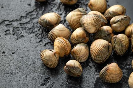 Fresh raw cockle molluscs in heart-shaped shells, sea food shellfish on dark background