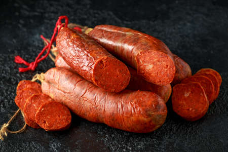 traditional Balearic raw cured meat sobrassada sausage made from ground pork, paprika and spices on rustic black background 版權商用圖片