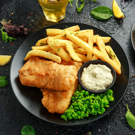 British Traditional Fish and chips with mashed peas, tartar sauce and cold beer