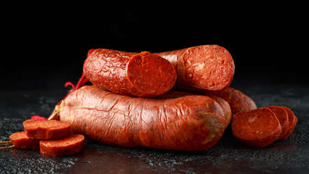 traditional Balearic raw cured meat sobrassada sausage made from ground pork, paprika and spices on rustic black background Reklamní fotografie