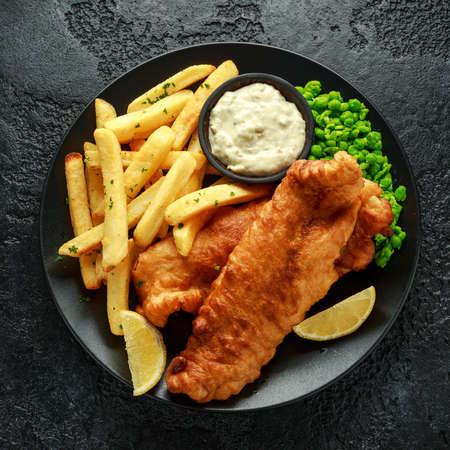 British Traditional Fish and chips with mashed peas, tartar sauce and cold beer.