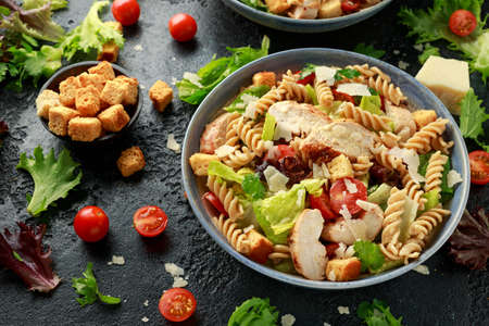 Caesar Salad Pasta with chicken, tomato, parmesan cheese and vegetables. Banco de Imagens