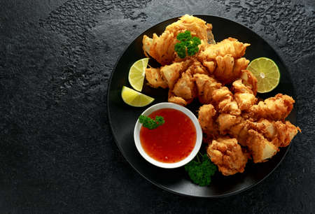 Fried Bloomin Onion with Chilli sauce and lime on black plate
