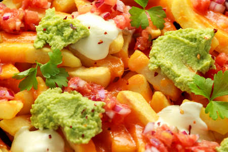 Loaded potato nachos with melted cheddar cheese, sour cream, tomato salsa, chilli, guacamole and beer.