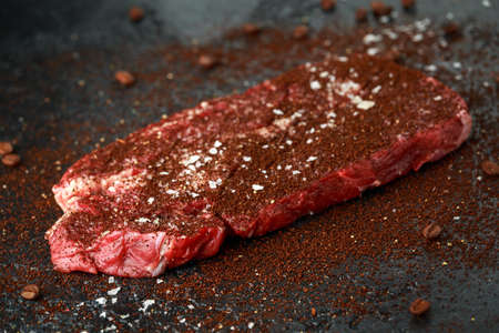 Ready to cook seasoned with home made coffee rub beef steak on dark background.
