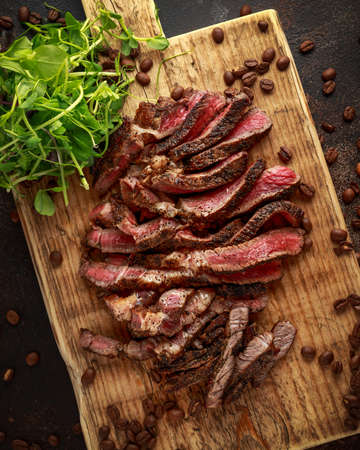 Freshly cooked seasoned with home made coffee rub sliced beef steak served on wooden board with green salad.