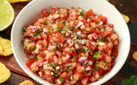 Mexican Tomato Salsa in white bowl with lime, red onion, jalapeno pepper, parsley and tortilla chips on wooden table.
