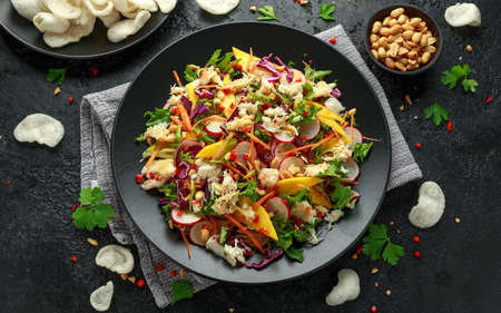 Crab salad with vegetables, radish, carrots, mango, pine nuts and prawn crackers.