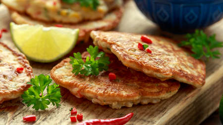 Corn fritters, pancake with dip white sauce, lime and chilli on wooden board.
