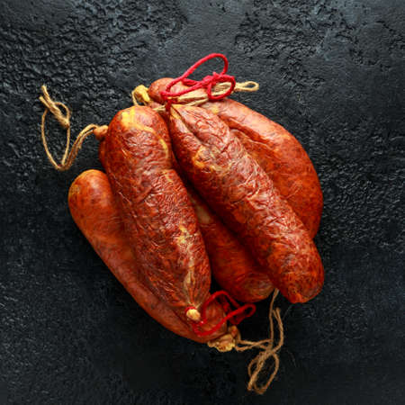 traditional Balearic raw cured meat sobrassada sausage made from ground pork, paprika and spices on rustic black background 스톡 콘텐츠