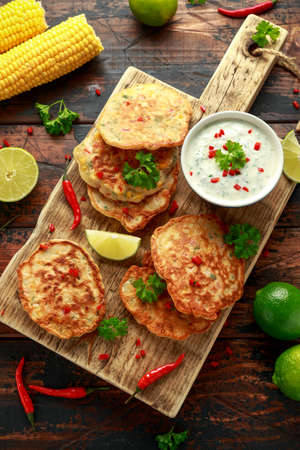 Corn fritters, pancake with dip white sauce, lime and chilli on wooden board Stock fotó