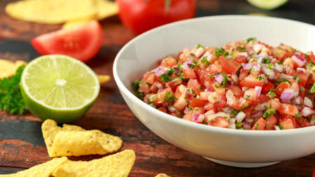 Mexican Tomato Salsa in white bowl with lime, red onion, jalapeno pepper, parsley and tortilla chips on wooden table 스톡 콘텐츠