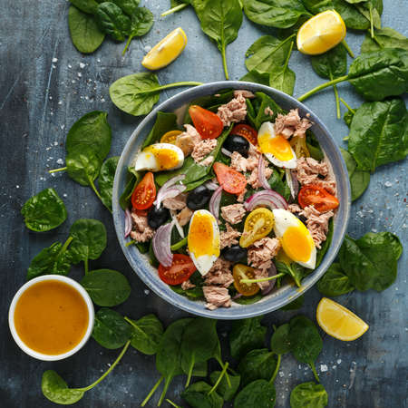 Protein packed tuna and soft, runny egg salad with pear shaped cherry tomatoes, black olives and spinach. 스톡 콘텐츠