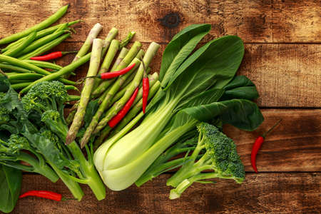 Variety of green vegetables pak choi, asparagus, broccoli and birds eye chilli on rustic wooden table