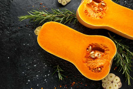 Fresh Butternut squash with rosemary, garlic, chilli flake and salt on black rustic background. 스톡 콘텐츠