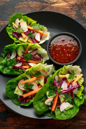Vegetable lettuce wraps with carrot, onion, radish, red cabbage, cucumber and sweet chilli sauce.