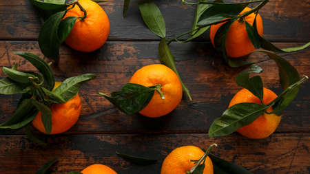 Mandarins Tangerines with green leaves on wooden table.