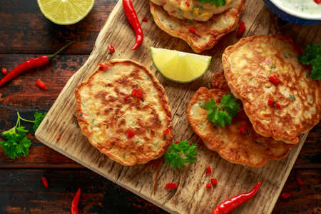 Corn fritters, pancake with dip white sauce, lime and chilli on wooden board 스톡 콘텐츠
