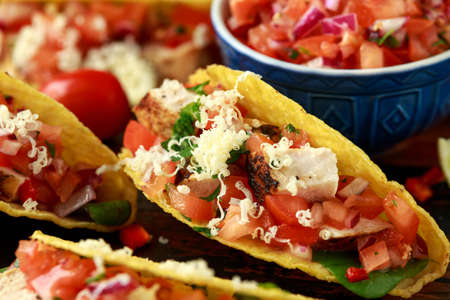 chicken tacos with salsa, cheese and corn tortila