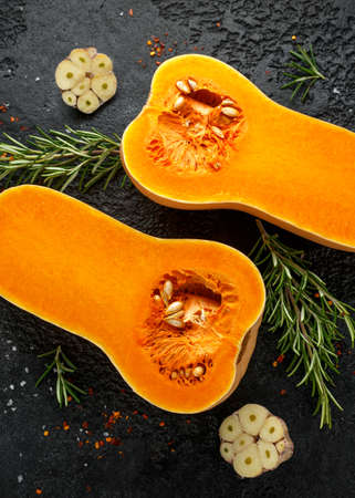 Fresh Butternut squash with rosemary, garlic, chilli flake and salt on black rustic background 스톡 콘텐츠