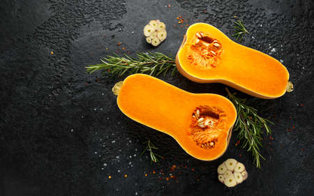 Fresh Butternut squash with rosemary, garlic, chilli flake and salt on black rustic background Standard-Bild