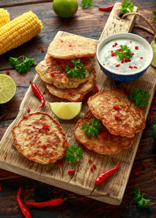Corn fritters, pancake with dip white sauce, lime and chilli on wooden board Zdjęcie Seryjne