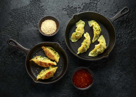 Steamed and Fried yaki Gyoza served on cast iron skillet, pan with sweet chilli sauce and sesame seeds
