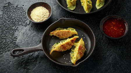 Steamed and Fried yaki Gyoza served on cast iron skillet, pan with sweet chilli sauce and sesame seeds. 스톡 콘텐츠