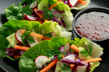 Vegetable lettuce wraps with carrot, onion, radish, red cabbage, cucumber and sweet chilli sauce