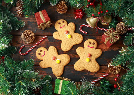Christmas Gingerbread Men with decoration, gifts, green tree branch on wooden rustic table